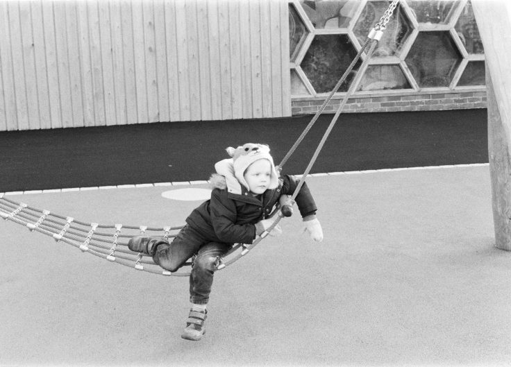 Black and white film photograph of child on hammock shot on Delta 400 film