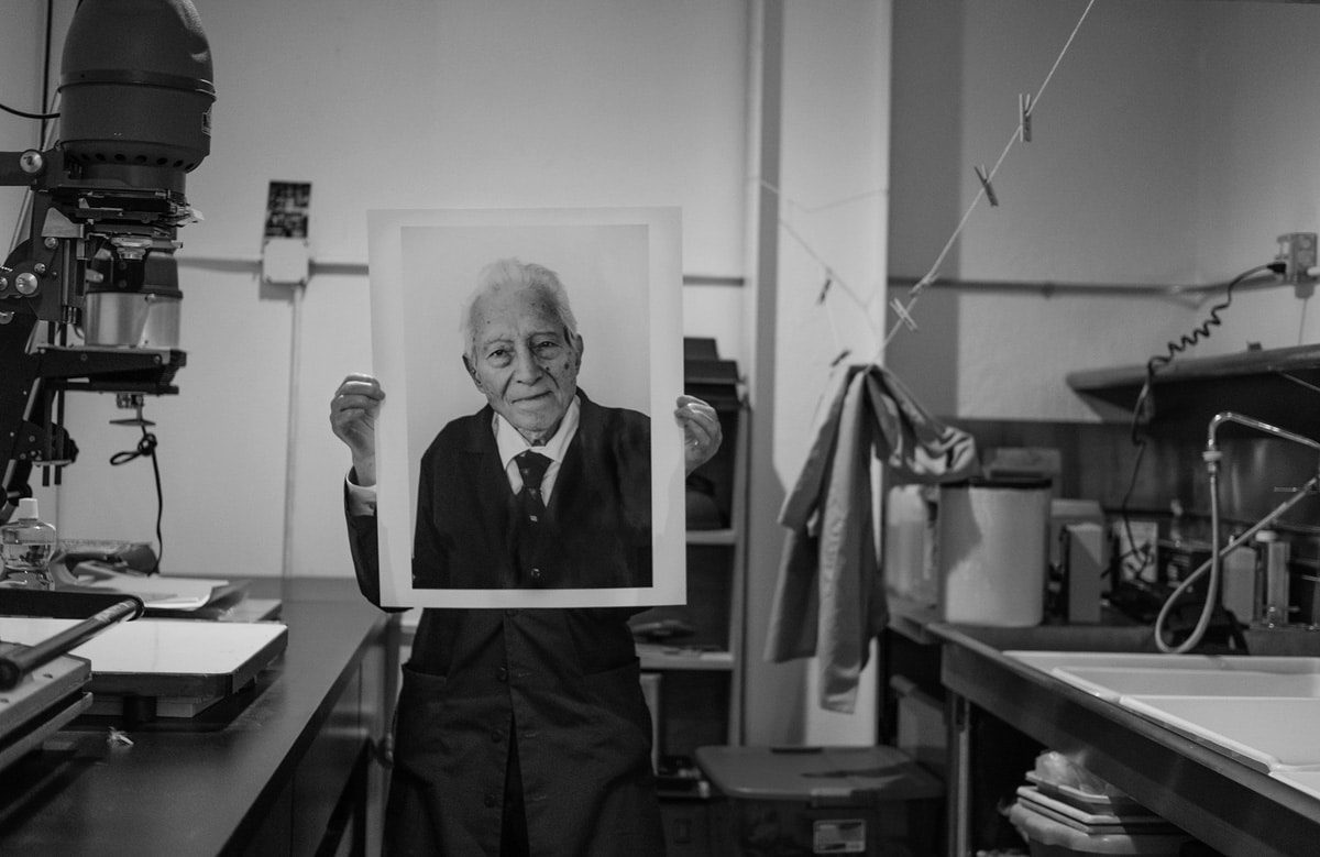 IMAGE: Tony Vaccaro holding a print of himself in his studio - https://emulsive.org/wp-content/uploads/2018/07/Tony-holding-Tony.jpg