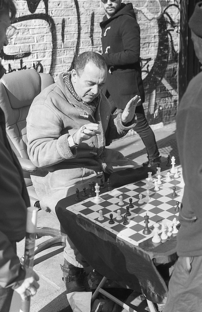 black and white film photo of man playing chess
