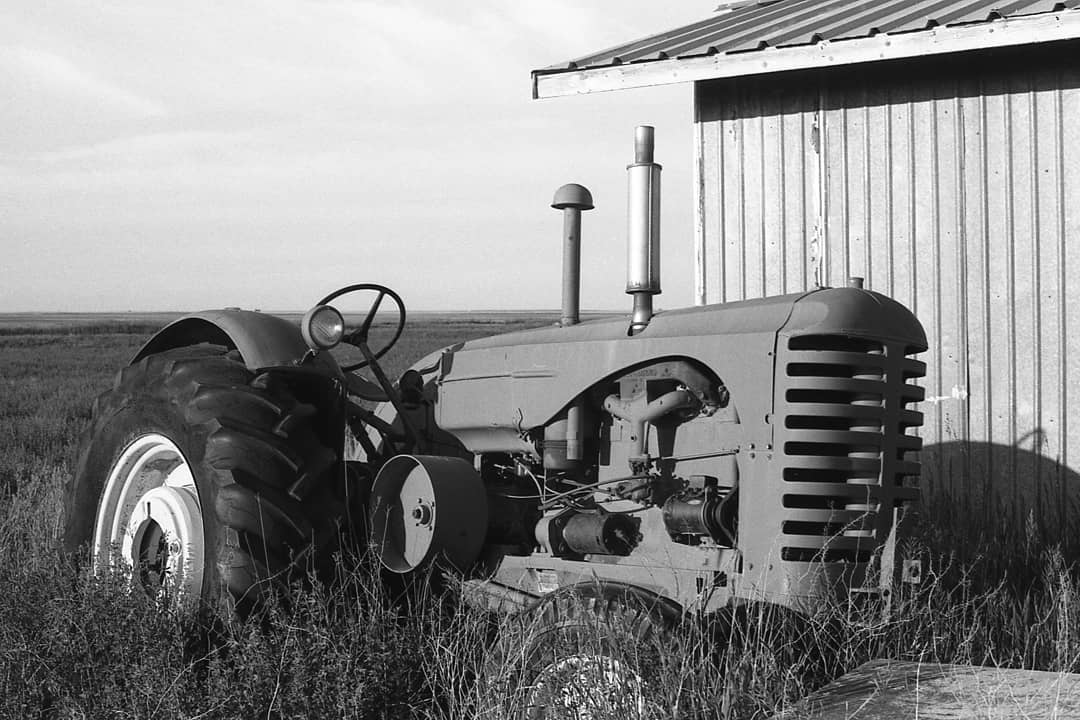 analogue_reverend Even old junk has a story. How many fields did this old tractor plow? Whose livelihood did it support? What did that farmer daydream about while he was driving it? . Shot on film: Canon AE-1; Ilford FP4 . #filmphotography #filmisnotdead #canonae1 #ilfordphoto #ilfordfp4 #rural #tractor #overlooked #analoguevibes #fridayfavourites