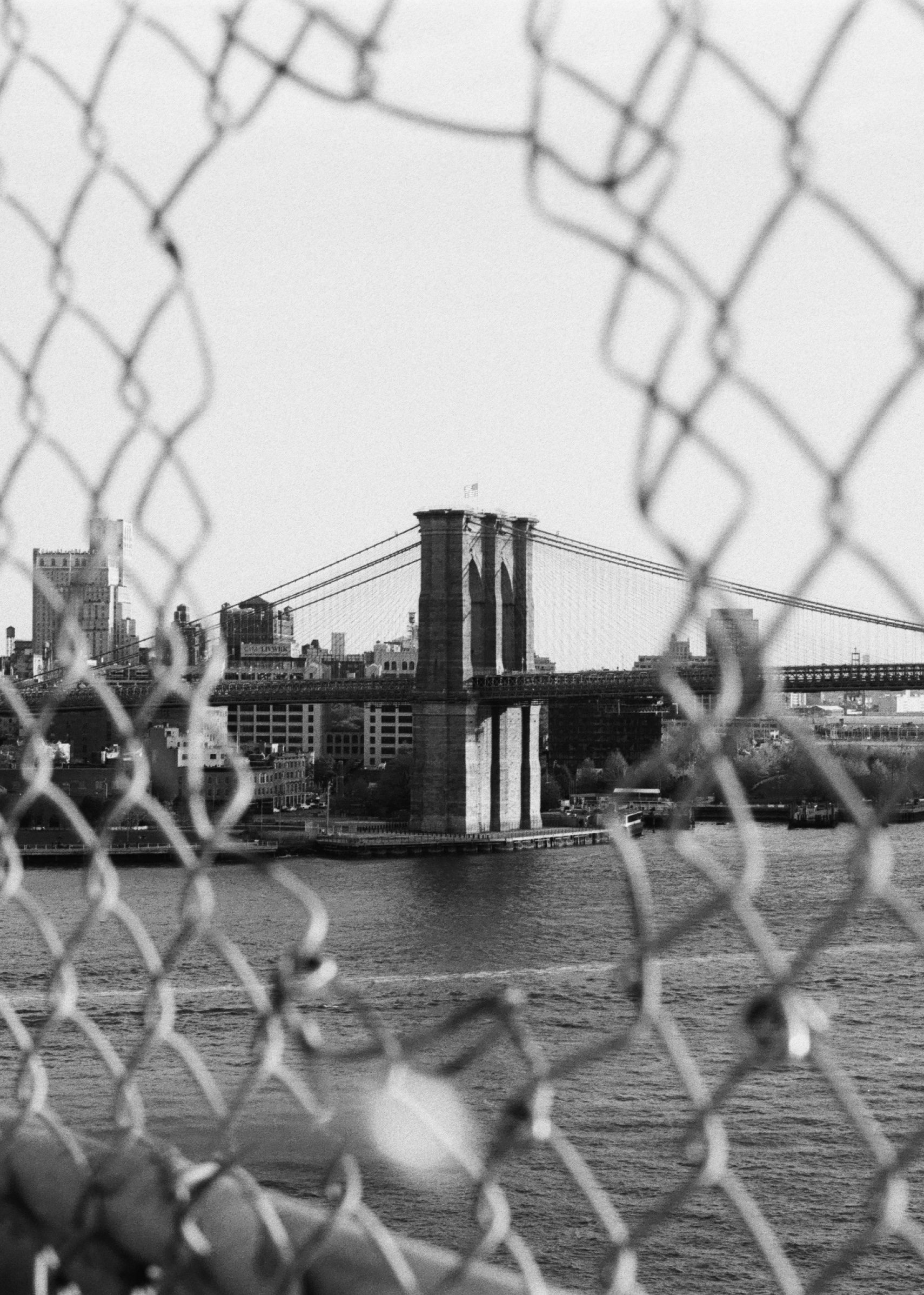 Brooklyn Bridge through the wire on HP5 black and white film by Louis Kassam