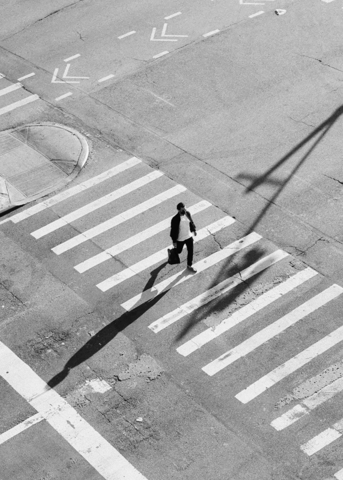 Pedestrian on zebra crossing shot on ILFORD HP5 plus black and white film by Louis Kassam