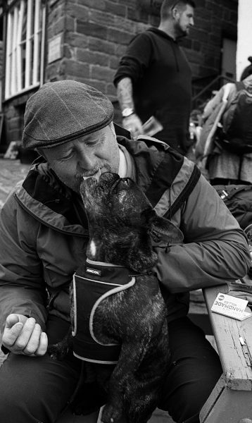 Man feeding doy in Robinhuds bay shot on ILFORD black and white film by Keith Moss