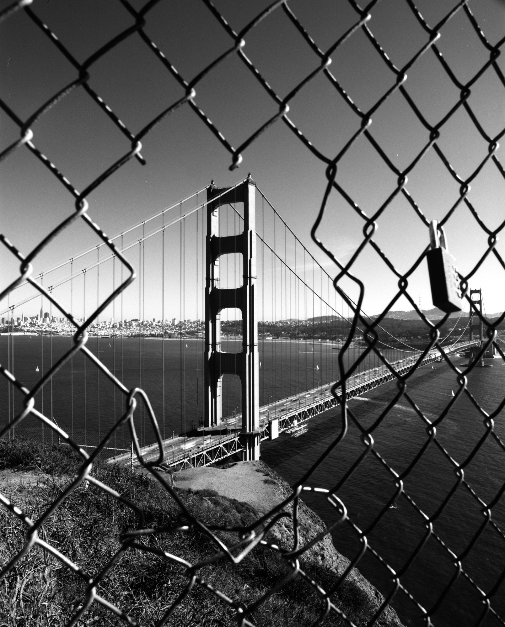 Golden gate bridge, framed through a gap in a wire fence. Shot on ILFORD Delta 100 black and white film by Sergio Lopez