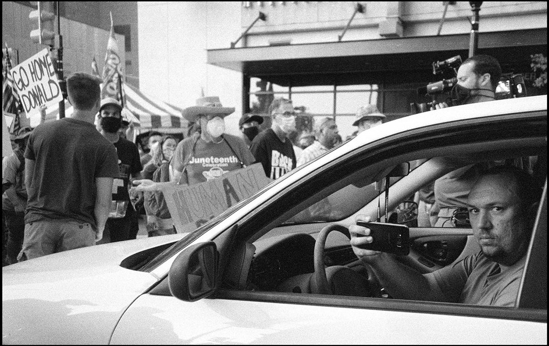 A man documents the chaos out side of Donald Trump's rally. Tulsa, OK. Ilford Delta 400.