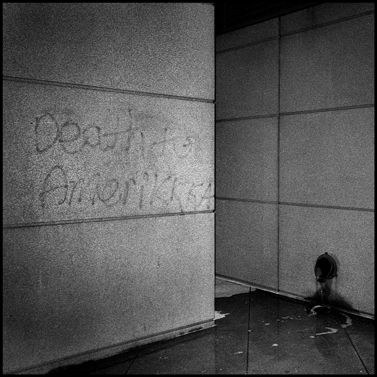"""The words, """"Death to Amerikkka"""" power washed from a building near the Colorado state capitol. Dencer, CO. Ilford Delta 400."""
