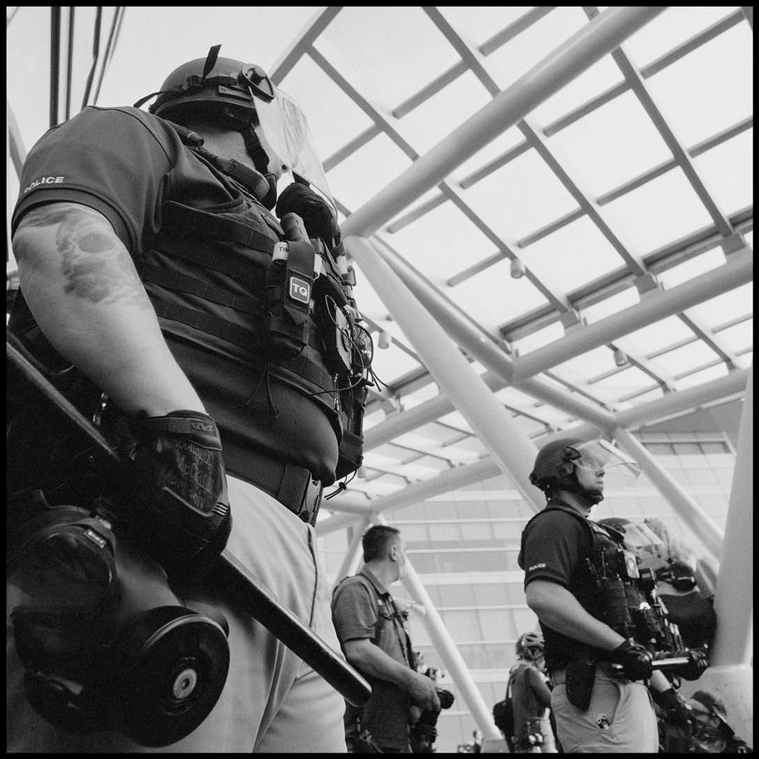 Police adorned in riot gear guarding the Salt Lake City Police Department. The building took heavy damage after protests erupted after George Floyd's death. Salt Lake City, UT. Ilford Delta 400.
