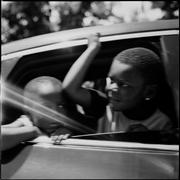 wo children look out the window as they drive by a protest, Salt Lake City, UT. Ilford Ortho Plus.