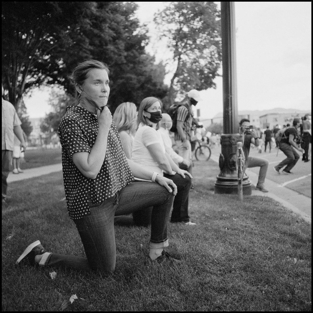 Salt Lake City Mayor, Erin Mendenhall, kneels as protestors march past the county building. Salt Lake City, UT. Ilford Delta 400.