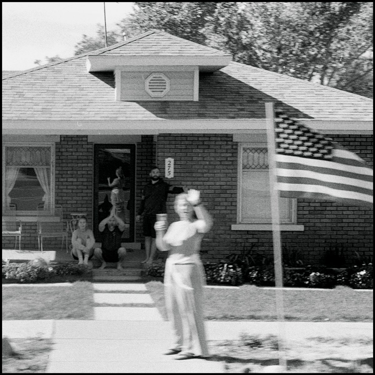 A family stands outside their home and watches a Pro Trump parade drive by. Hurricane, UT. Ilford Delta 400.