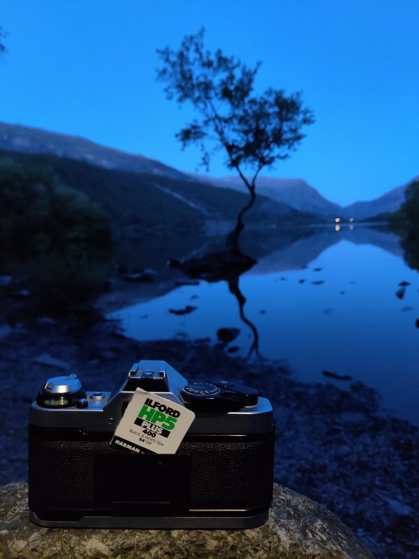 The back of the Canon AE-1 camera at the edge of Padarn lake, Llanberis. With the lonely tree in the background. Shot on a OnePlus 7T.